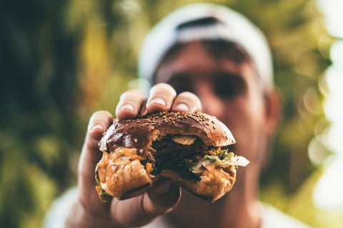 Closeup of a man holding a burger that he has bitten out of
