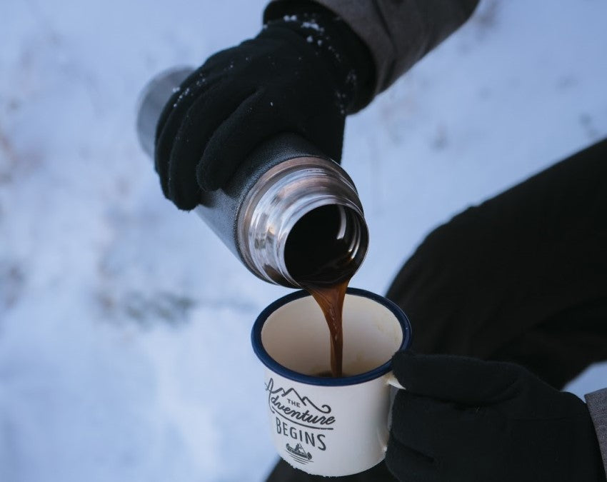 portable coffee maker pouring mug of coffee in snow