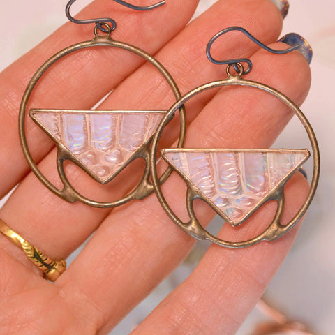 A pair of triangular and circular iridescent snakeskin shed earrings held in bright light.