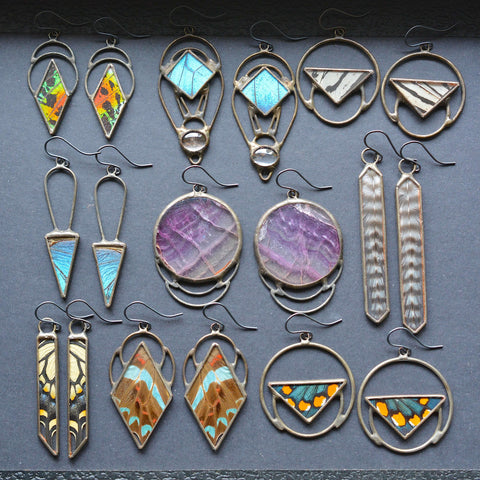 earrings that are colorful and made with butterfly wing, feathers, and gemstones arranged in rows in a black tray.