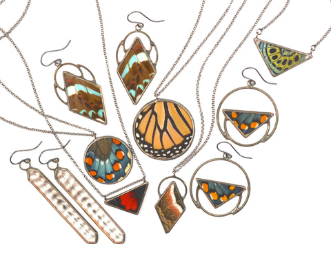 colorful butterfly and striped feather jewelry in various geometric designs arranged on a white background.