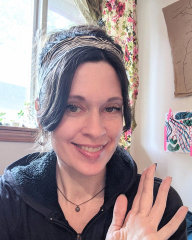 The owner and designer of HartVariations - a woman with dark bangs in a black hoodie wearing a zebra headband waving to the camera in front of a luminescent window.