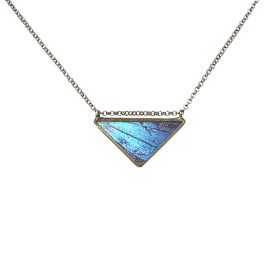 Blue triangle butterfly wing necklace photographed against a white background.