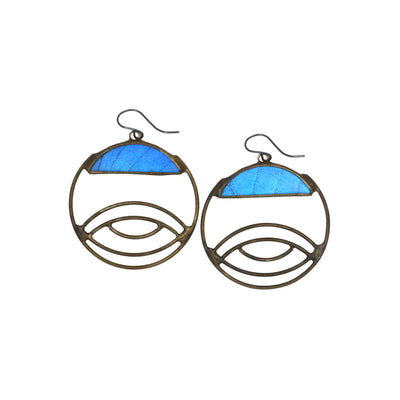 circular earrings with eye shaped metalwork resting below blue butterfly wings photographed against a white background.