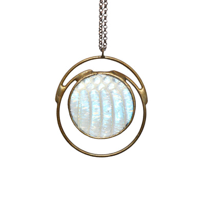 Iridescent snakeskin shed glistens blues and light greens encased in round glass. Darkened silver metal curves crescents below and above the serpentine, iridescent orb.