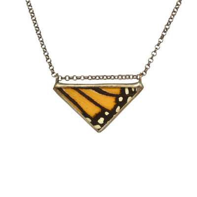 A striking, cruelty free orange, black, and white striped and spotted Monarch butterfly wing triangle necklace hanging against a white background.