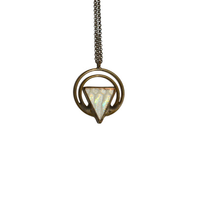 iridescent geometric necklace with really colorful snakeskin shed shown against a white background, hanging in the sun.