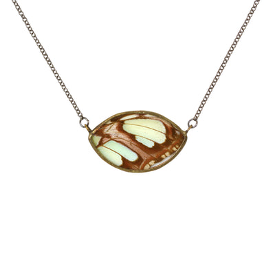 A necklace of mint green and brown butterfly encased in an eye shaped frame of glass and metal pictured against a white background.