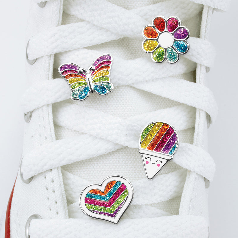 CHARM IT! Rainbow Shoelace Charms includes a Glitter Rainbow Flower Shoelace Charm, a Glitter Rainbow Heart Shoelace Charm, a Glitter Rainbow Snowcone Shoelace Charm, and a Glitter Rainbow Butterfly Shoelace Charm