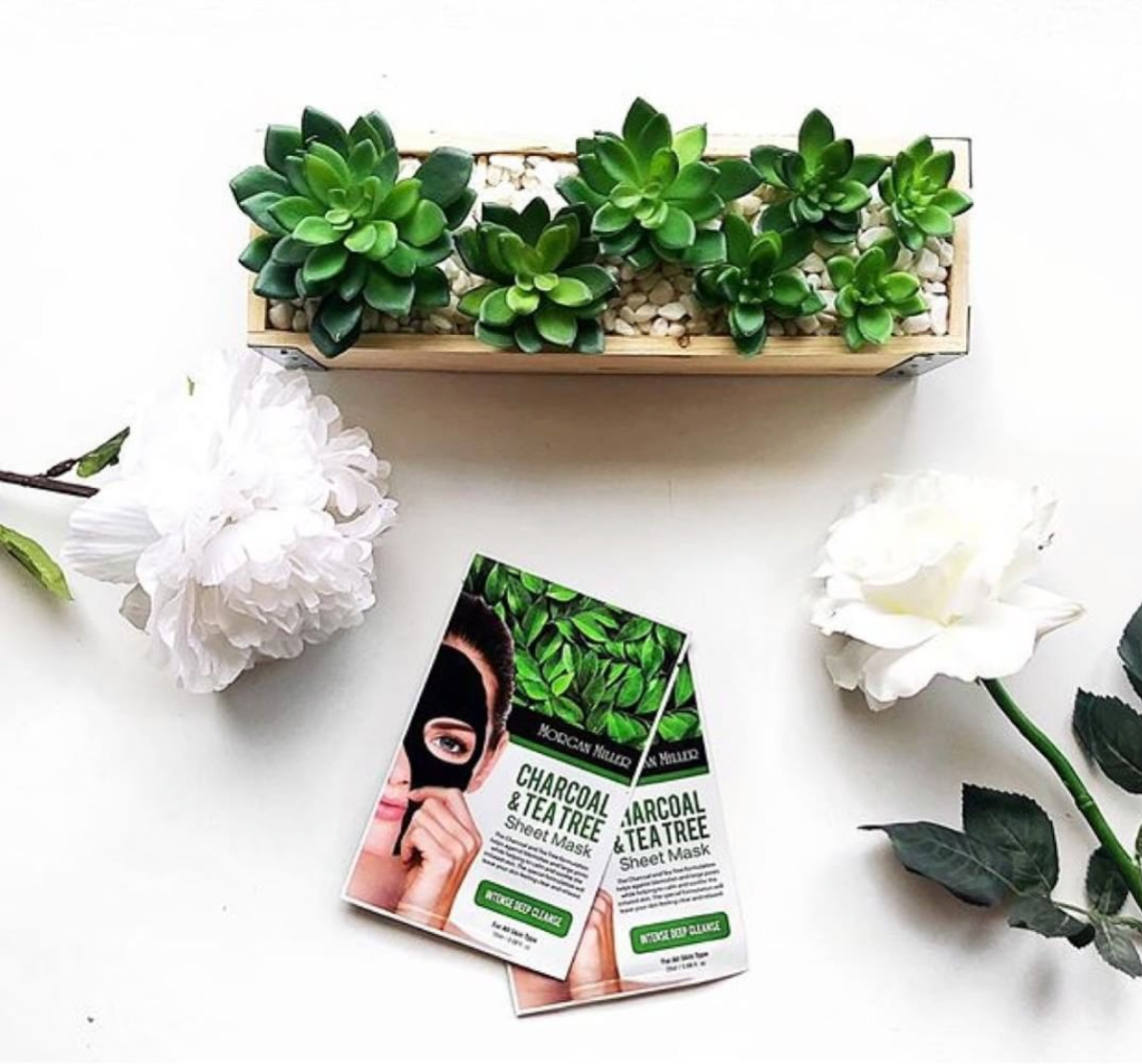Flatlay view of Morgan Miller's Charcoal & Tea Tree Sheet Masks with flowers