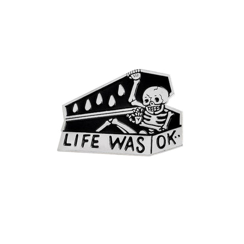 Silver and black Life Was Okay Enamel Lapel Pin of skeleton closing casket.