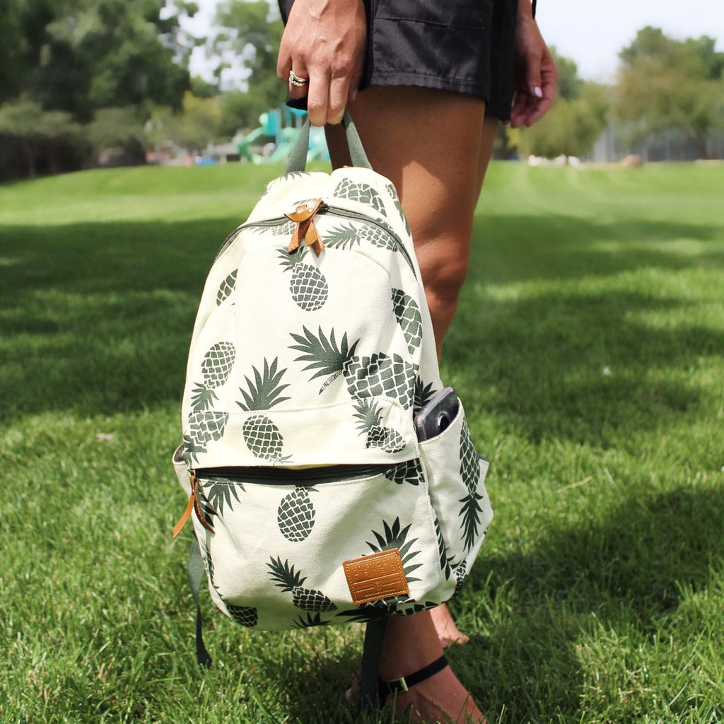 Woman holding pineapple spotted backpack ouside