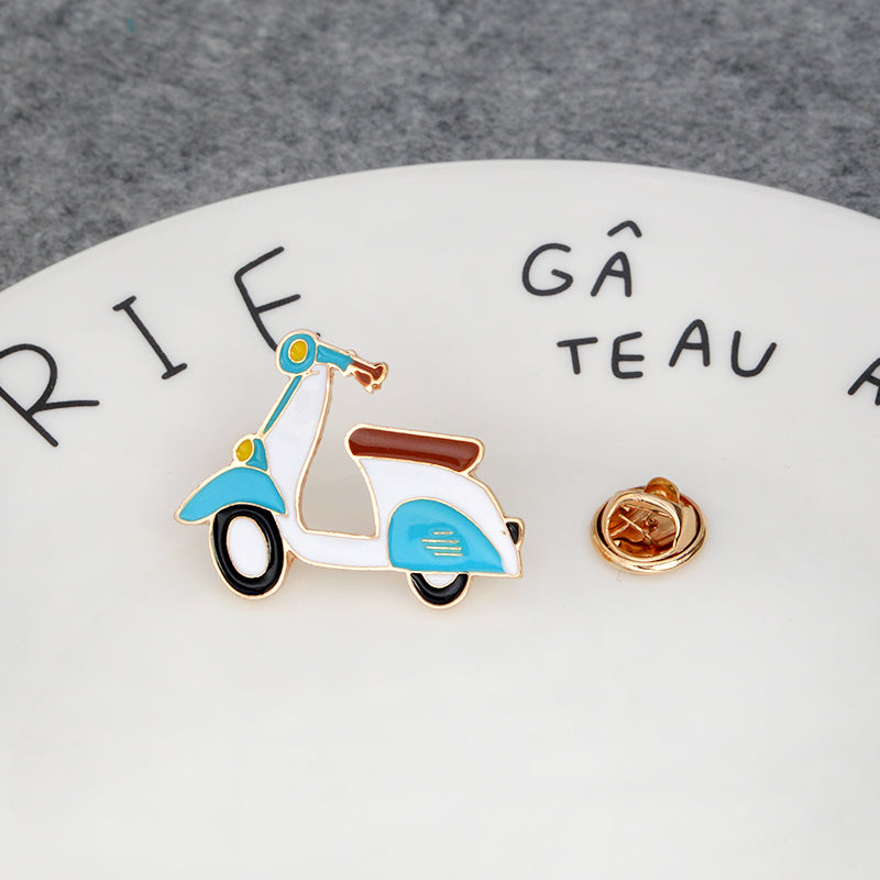 Blue and white enamel lapel moped scooter pin with black and white wheels placed on a plate.
