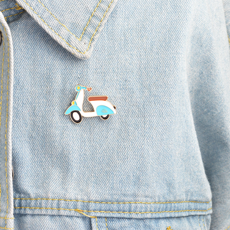 Blue and white enamel lapel moped scooter pin with black and white wheels attached to blue jacket.