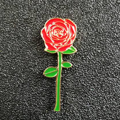 An enamel lapel designed rose with a green stem and red pedals.