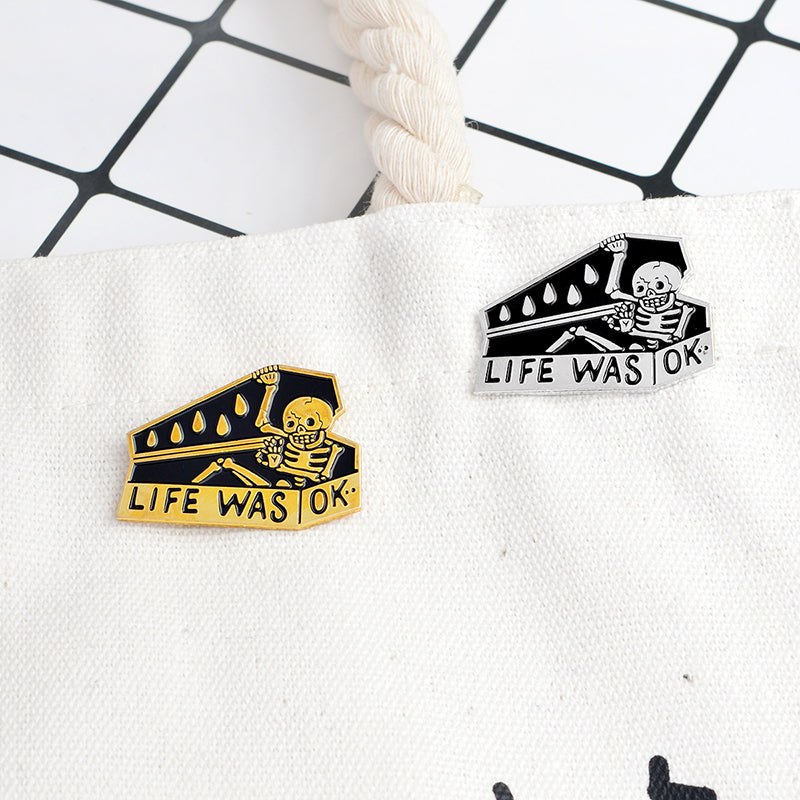 One Silver and black and one golden and black Life Was Okay Enamel Lapel Pin of skeleton closing casket pinned on white bag.