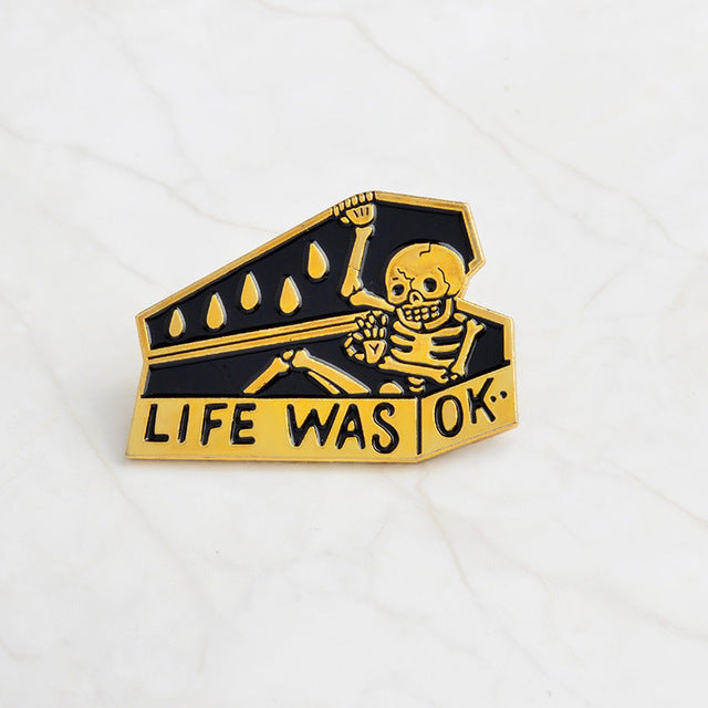 Gold and black Life Was Okay Enamel Lapel Pin of skeleton closing casket.