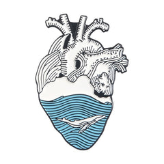Heart shaped enamel lapel pin with engraved with a whale in ocean design black, blue and white.