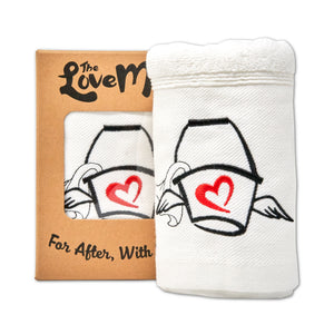 The Love Mop Sex Towel in kraft gift box. The gift box has a clear window showing the embroidery on the towel.