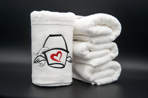 A stack of folded/rolled up Love Mop Sex Towels.  the upright towel is showing the Love Bucket embroidery