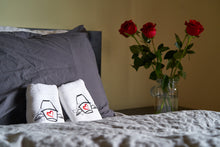 two Love Mop sex towels, folded and set on a bed. Bouquet of red roses on the bedside table