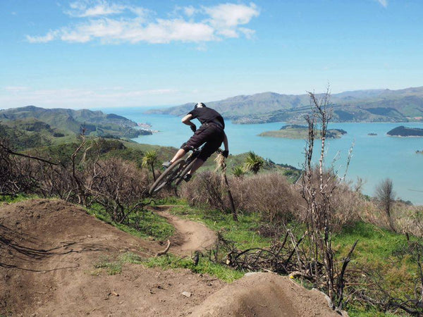 Mountain biker jumping with background of hills and harbor