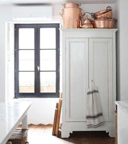 white armoire with copper
