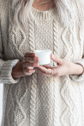 woman in white sweater with lotion