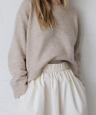 blond girl in beige sweater white pants