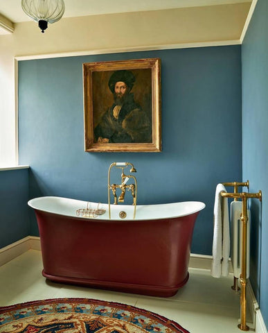 blue walls with portrait and red bathtub