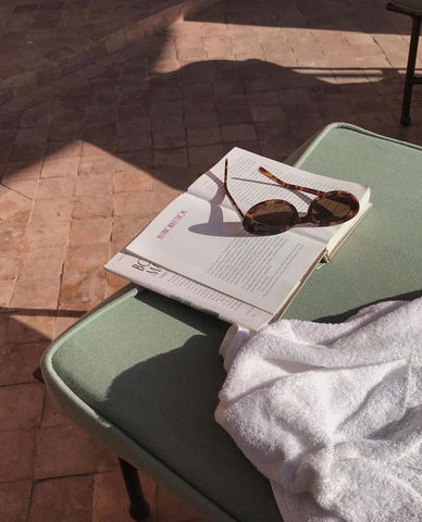 book and sunglasses with green pillow