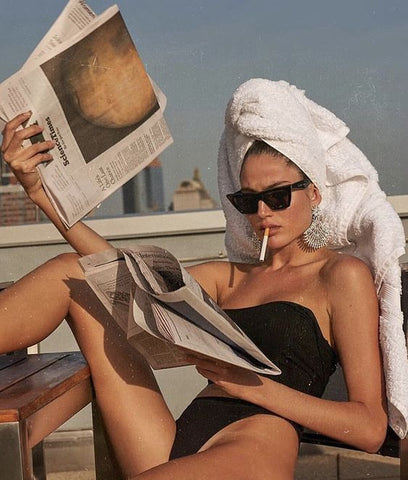 woman reading newspaper in a towel