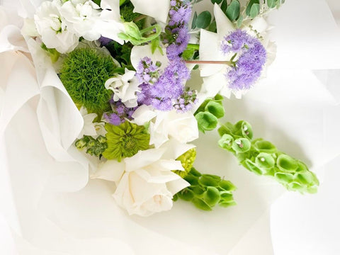 arrangement of flowers green purple white