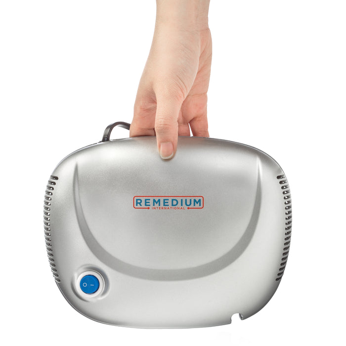 Hand holding Remedium International - Compressor Nebulizer System from its top