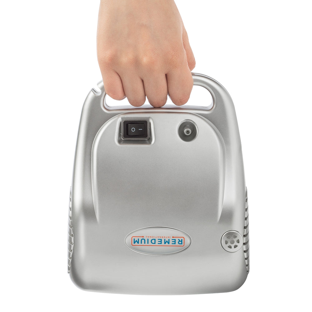 A hand holding the BreatheEasy Deluxe Compressor Nebulizer System from it's handle with buttons