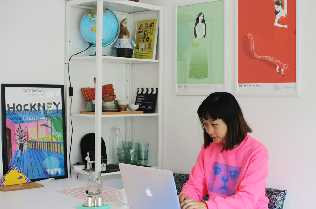 Qian working with her art in the background