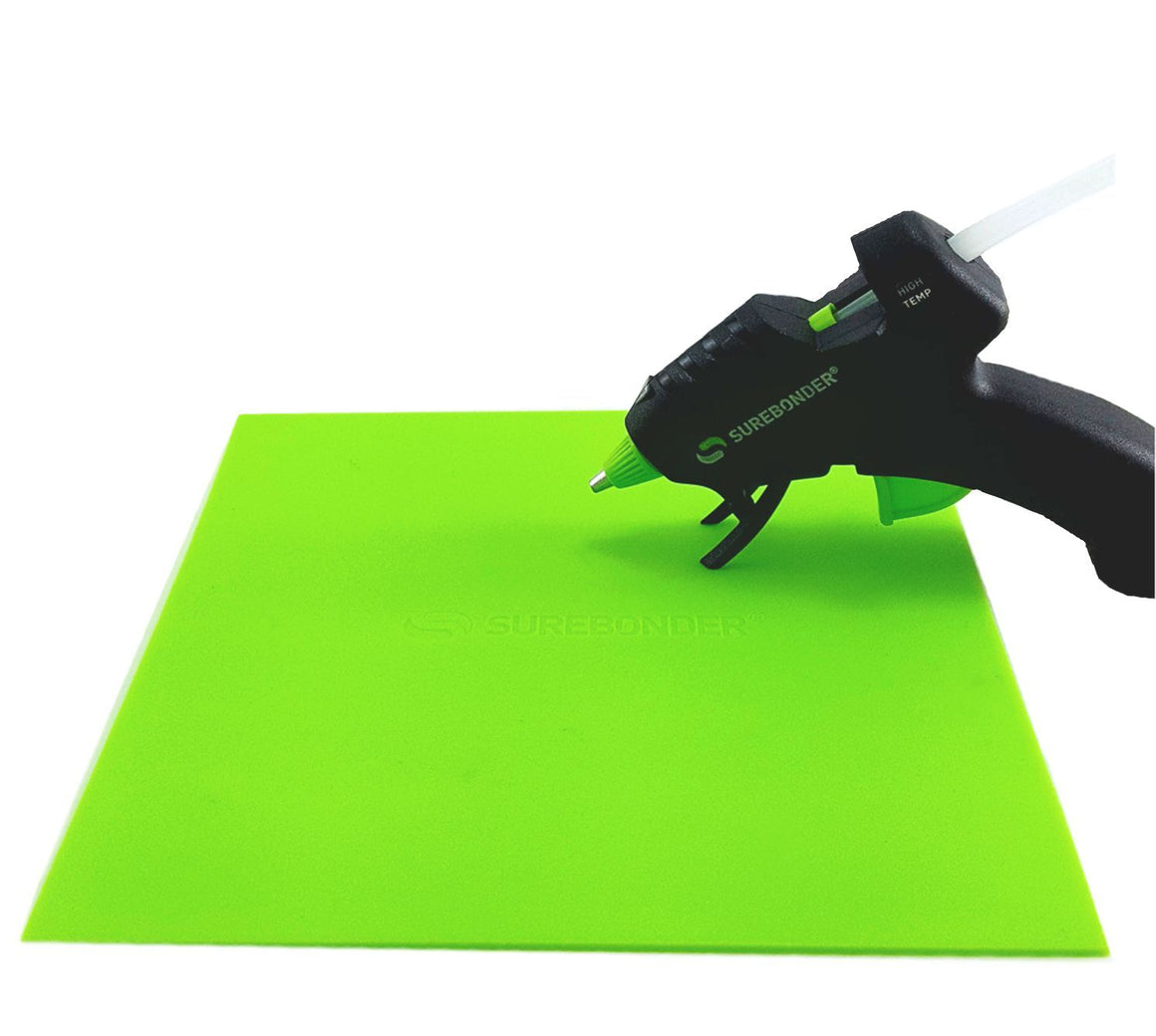 Hot glue gun hovers over a green Surebonder silicone pad, measures 8 inches by 8 inches