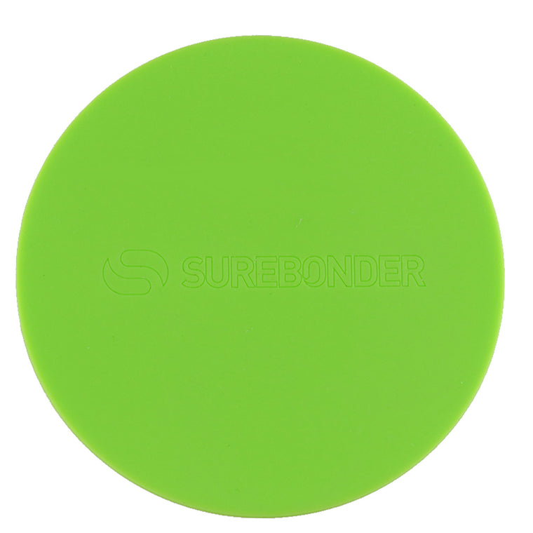Hot glue gun hovers over a round green Surebonder silicone pad, measures 4 inches diameter