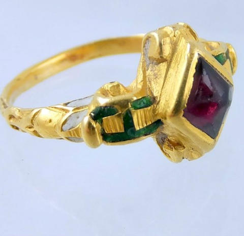 A gold and garnet engagement ring accented with enamel