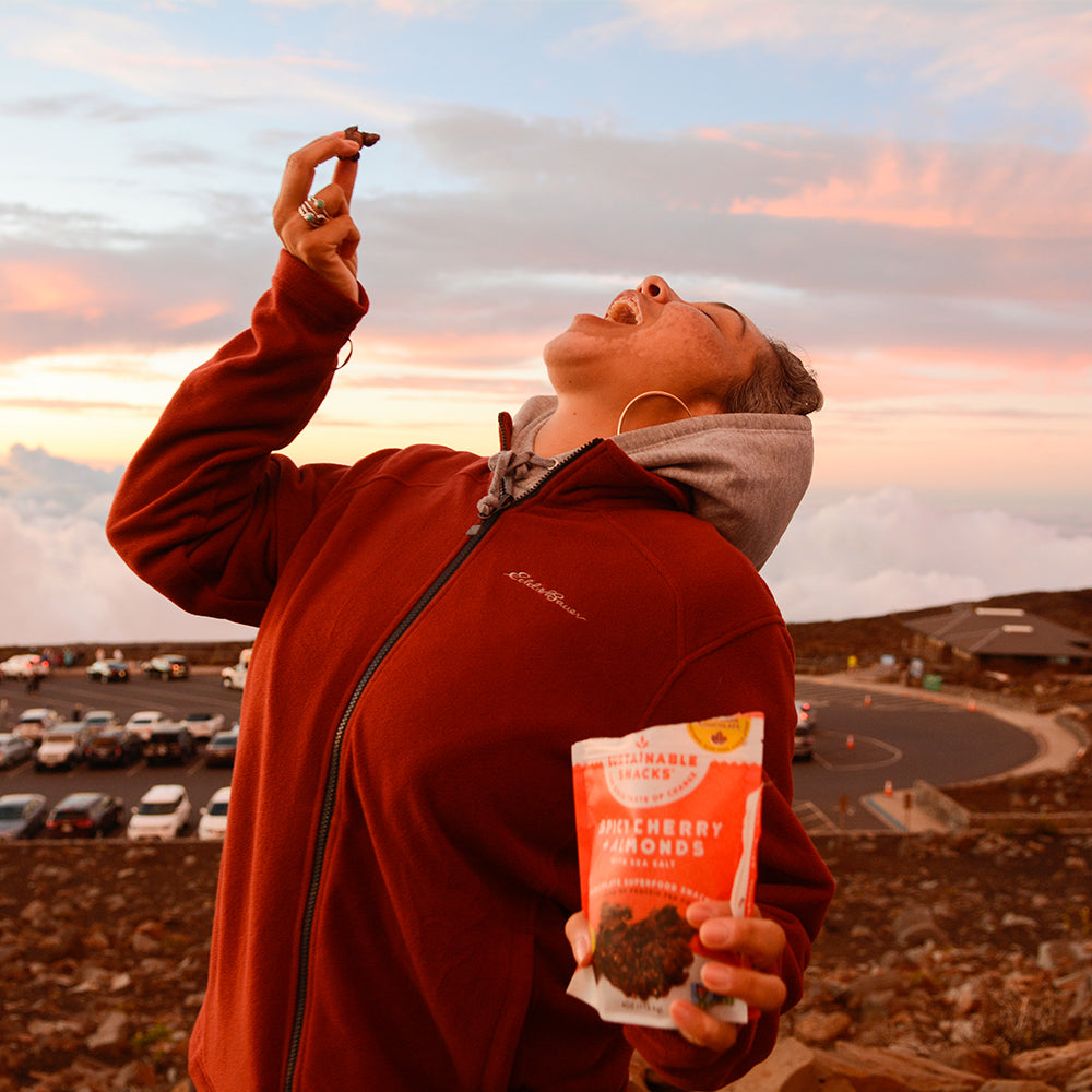 Women enjoying spicy cherry + almonds chocolate superfood clusters on top of volcano in Hawaii