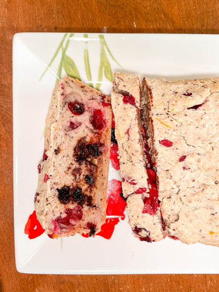 Sliced Cranberry & Orange Loaf on white plate on wooden table