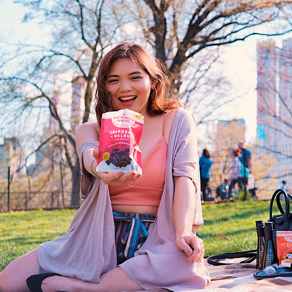 Young women in central park holding cranberry + walnuts chocolate superfood clusters