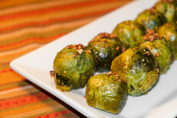 9 brussel sprouts topped with roasted pecans chopped to look like breadcrumbs on white platter on orange, red, and green stripped table cloth