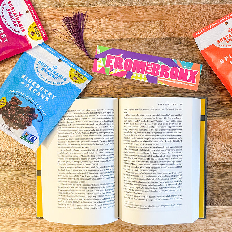 Open Guy Raz book on wooden table with From The Bronx book mark and three bags of chocolate superfood snacks from Sustainable Snacks