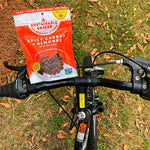 Spicy Cherry + almonds bag of chocolate superfood clusters on bike riding on grass