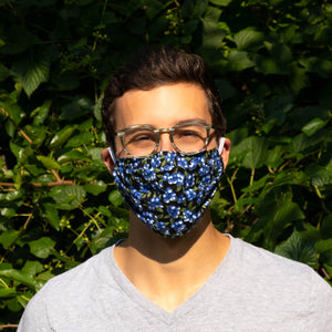 Man in Sustainable Snacks upcyled blueberry mask in front of tree