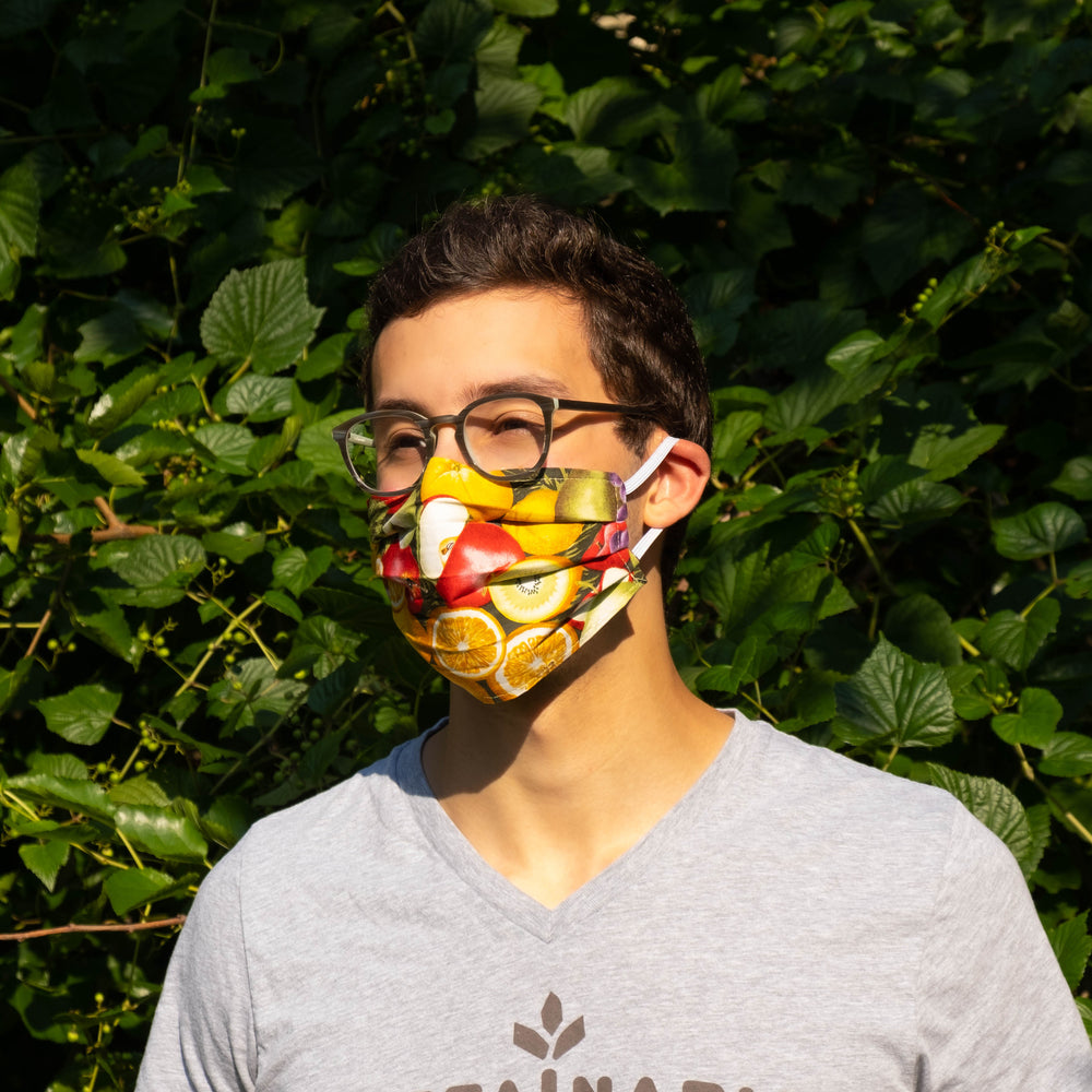 Man in Sustainable Snacks upcyled fruit mask in front of tree