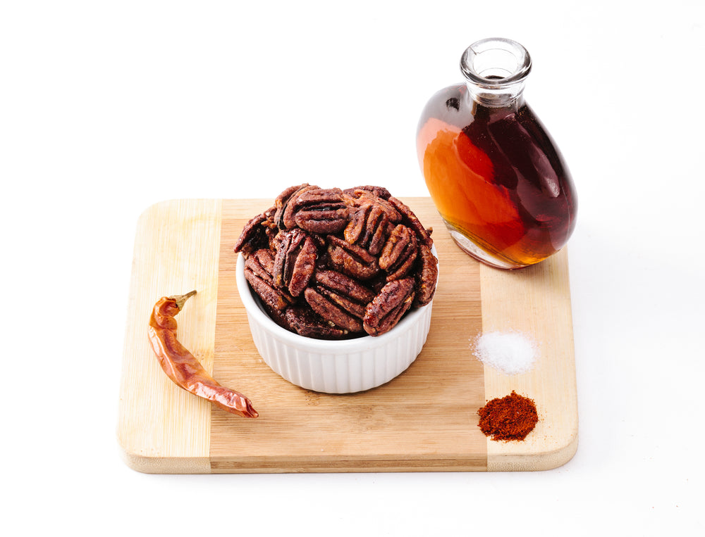 Bowl of smoky maple pecans on wooden cutting board with spices and maple syrup in glass bottle