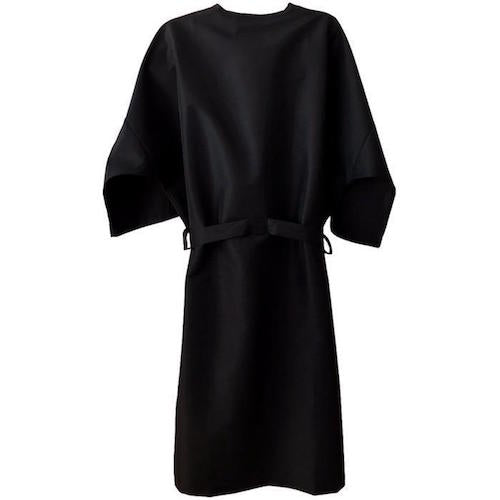 Black, kimono-style client wrap/robe/gown. Product closes in the front with three stainless steel snaps and a long attached belt for complete coverage. The wraps come in two sizes; Regular & XL, both sizes have two deep pockets, and ¾ length sleeves. The fabric is nylon/polyester making the product water repellent, stain resistant, and washer and dryer safe.  Rear view of the product.
