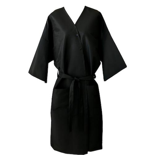 Black, kimono-style client wrap/robe/gown. Product closes in the front with three stainless steel snaps and a long attached belt for complete coverage. The wraps come in two sizes; Regular & XL, both sizes have two deep pockets, and ¾ length sleeves. The fabric is nylon/polyester making the product water repellent, stain resistant, and washer and dryer safe.  Front view of the product.